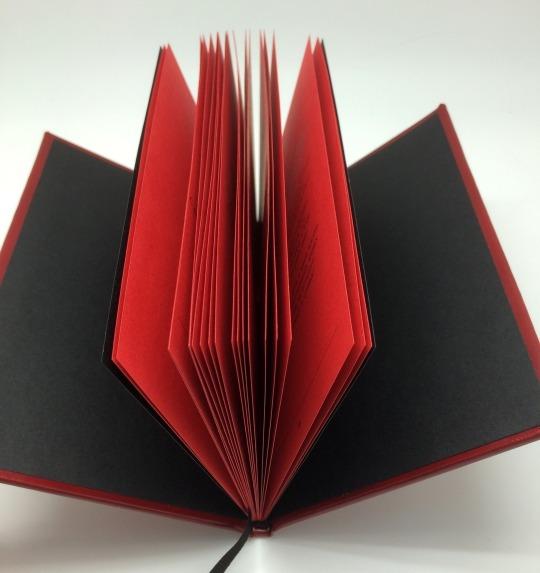 Красный переплет, черное тиснение, расные страницы, черный текст. Красное ляссе, чёрный каптал.